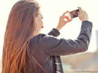 fata care isi face un selfie in soare