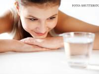 femeie cu un pahar de apa in fata