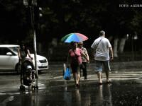 Trecatori surprinsi de ploaie in cartierul Militari din Capitala.