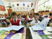 Mai multi copii din clasa 1C a Scolii Gimnaziale Aurel Vlaicu din Fetesti, judetul Ialomita, rasfoiesc manualele primite cu ocazia inceperii anului scolar preuniversitar 2016-2017.