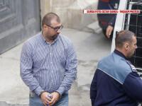 Fostul ofiter SRI, Daniel Dragomir, este escortat de un politist la iesirea din sediul Curtii de Apel Bucuresti, miercuri, 21 septembrie 2016