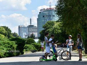 Mai multi copii joaca Pokemon GO pe telefonul mobil, in parcul Herastrau din Bucuresti.