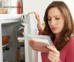 femeie se uita la alimente in frigider