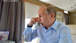 Vladimir Putin vorbind la telefon in avion