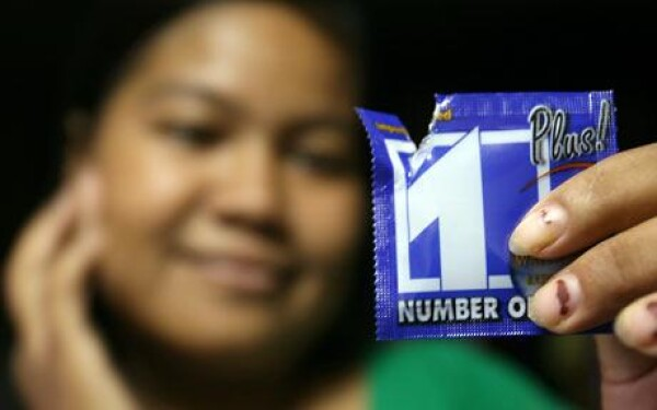 Photo AFP / GETTY. A Cambodian worker holds a Number One Plus condom