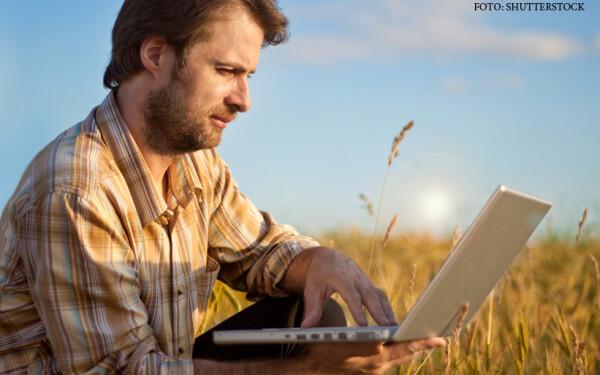 barbat cu laptop in mana pe camp