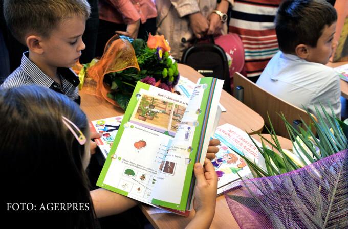 elevi in prima zi de scoala cu manualele in mana
