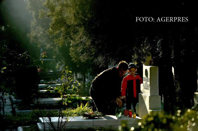 Un barbat insotit de un copil aprind lumanari la un mormant din Cimitirul Eroii Revolutiei.