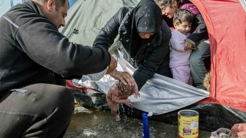 Imaginea care a facut inconjurul lumii. Momentul in care un bebelus este spalat in mocirla, intr-o tabara de refugiati