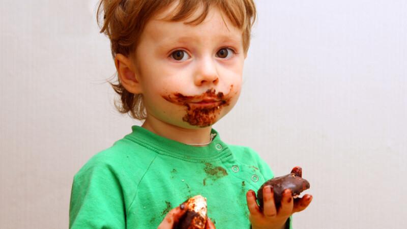 copil care mananca ciocolata