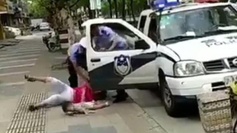 Femeie cu un copil în brațe, trântită la pământ de un polițist. Motivul disputei