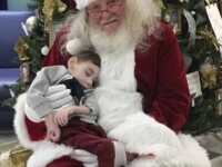 Poza care a devenit viral: un copil bolnav stă așezat în poala lui Moș Crăciun