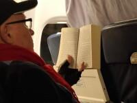 Mihai Lucan, fotografiat în avion de un pasager, în ziua de Crăciun. Cartea pe care o citea medicul