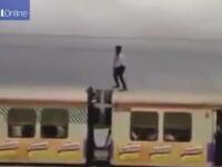 Cascadorie riscanta in India. Un barbat a facut echilibristica pe un tren in miscare, la cativa centimetri de cabluri