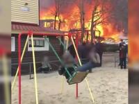 Momentul în care un băiat se dă în leagăn în timp ce casa din spatele său arde