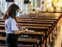 Un voluntar din Filipine pune semne pe băncile din biserici, pentru a asigura că se respectă distanțarea socială