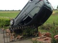 O masina a ramas in pozitie verticala in urma unui accident, dupa ce soferita a trecut cu roata peste o groapa. FOTO