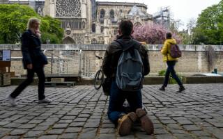 Un parizian, surprins în timp ce se roagă în genunchi în fața Catedralei Notre Dame