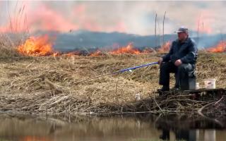 """Un bărbat pescuia liniștit în timp ce câmpul ardea în spatele lui. """"Nu e nimic nou aici"""""""