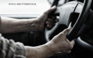 sofer de TIR in cabina cu mainile pe volan