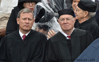 Supreme Court Justice Stephen Bryer(L) assists Justice Ruth Bader Ginsburg(2nd-L) with a rain poncho during inauguration ceremonies for President-elect Donald Trump