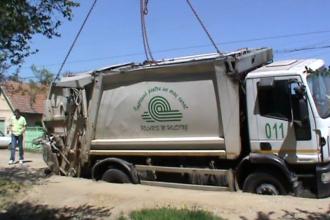 Drum surpat intr-un cartier din Arad. O masina de ridicat gunoiul a ramas blocata intr-o groapa