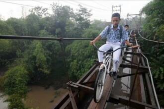 Cel mai periculos drum spre scoala: Copiii merg cu bicicleta pe scandurile de lemn ale unui pod suspendat