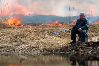 """Un bărbat pescuia liniștit în timp ce câmpul ardea în spatele lui. """"Nu e nimic nou aici"""" VIDEO"""