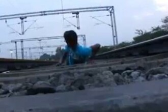 Moartea, luata in ras. Sta intins pe sine in timp ce trenul trece peste el. VIDEO sinonim cu nebunia