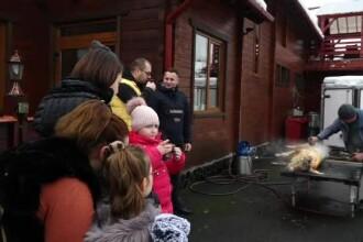 Turiştii fac live pe Facebook cu pomana porcului. Copiii, aduşi să vadă cum e pârlit