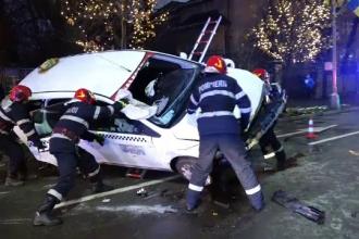 Taxi răsturnat pe o stradă din Baia Mare. Autoturismul a lovit o bordură și a rupt un copac