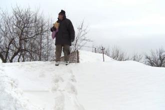 Buzoienii spun ca aceasta e cea mai aspra iarna din ultimii 10 ani. Un barbat, obligat sa urce un zid de zapada de 5 metri