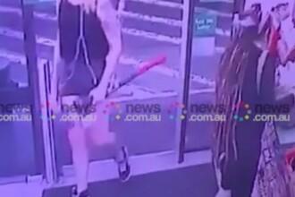 O femeie a intrat intr-un magazin, cu un topor, si a atacat doi clienti. VIDEO