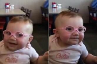 Un bebelus isi vede clar parintii pentru prima data, dupa ce isi pune ochelari. Reactia fetitei. VIDEO