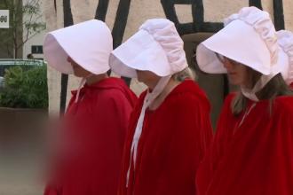 Semnificația din spatele pelerinelor roșii și bonetelor albe purtate de protestatarele din întreaga lume