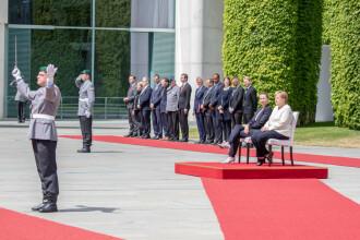 Merkel a stat pe scaun în timpul intonării unor imnuri de stat, din cauza tremuratului