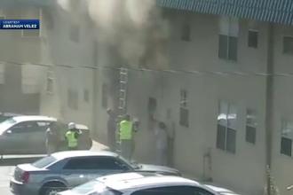 Momentul în care doi muncitori salvează copiii dintr-un apartament în flăcări