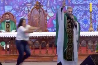 Momentul în care o femeie împinge un preot de pe scenă, în timpul predicii