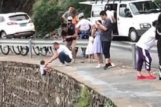 Inconștiență fără margini. Și-a ținut copilul pe marginea unei stânci, pentru a-i face o poză. VIDEO