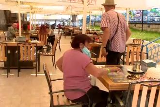 Distanțarea socială îi lasă flâmânzi pe turiști. Fug cu farfuria de mâncare când îi prinde ploaia