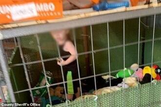 Un copil de 1 an a fost găsit închis într-o cușcă, înconjurat de șerpi și alte sute de animale
