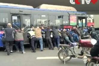 Un barbat din China a fost scos de sub rotile unui autobuz de catre pasageri si trecatori. VIDEO