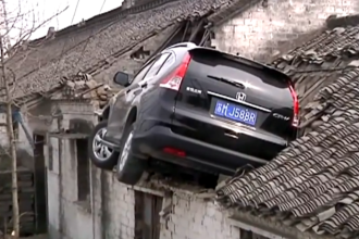 Un barbat a ajuns cu masina pe acoperisul unei case si a ramas blocat in autoturism. Cum a coborat dupa incident. VIDEO