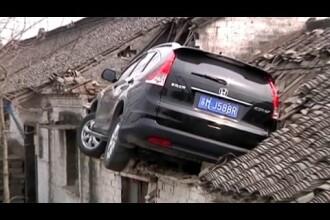 Soferul unui SUV a ajuns pe acoperisul unui case dupa ce a derapat. Imaginile surprinse de o camera de supraveghere