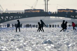 Localnicii se plimbă pe râul înghețat care trece prin centrul Sankt Petersburgului