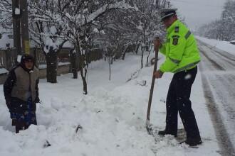 Bătrână izolată în curte din cauza zăpezii, ajutată de un polițist, în Gorj