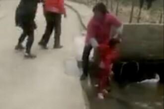 Momentul în care o femeie împinge un copil într-un şanţ cu apă. Incidentul a fost filmat de un trecător