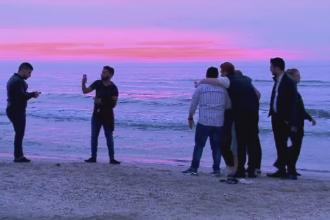 Rasaritul i-a prins pe plaja pe petrecaretii din Mamaia. Unii au facut fotografii, iar altii s-au racorit in valurile reci