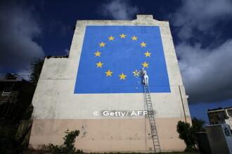 Un muncitor inlatura una dintre cele 12 stele aurii de pe drapelul UE. Unde a aparut noua lucrare a artistului urban Bansky