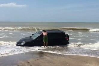 A ramas cu masina blocata in nisip in timp ce se plimba la malul marii. Cate persoane au intervenit sa rezolve problema VIDEO